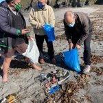 Vecinos de Navia recogen la basura que el mar deposita a pie de playa